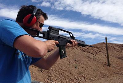 man shooting a machine gun