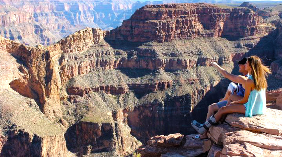 Couple sitting at Eagle Point at Grand Canyon west Rim