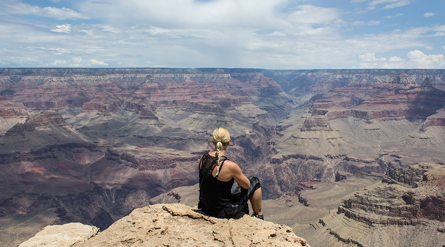 Girl sitting on the ledge of Grand Canyon