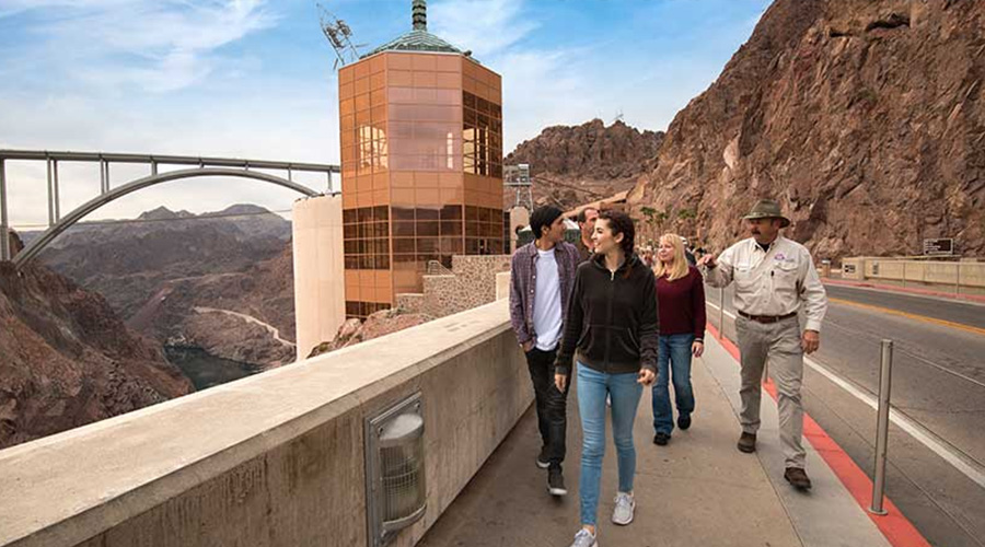 Guest and guide strolling across Hoover Dam