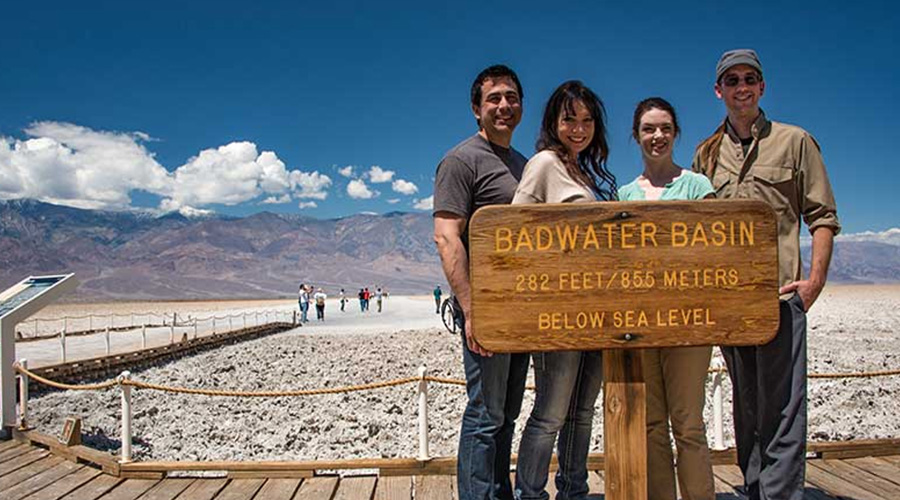 Guest posing behind sign at Badwater Basin Death Valley
