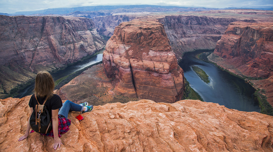Guest sitting on the clefts at Horseshoe Bend