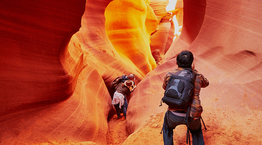 Photographer and guest in lit slots at Antelope Canyon