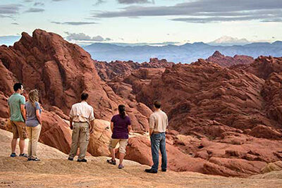 Pink Jeep guest and guide gazing out over the Valley of Fire rock formations 2