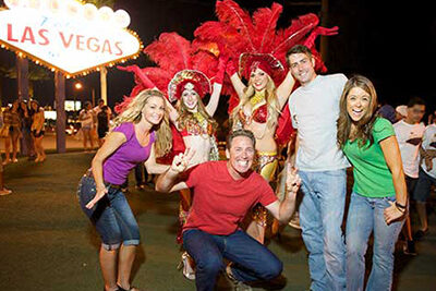 Show girls posing with guest at Las Vegas Sign