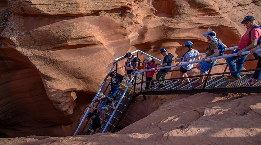Tourist climbing down stairs at Antelope Canyon