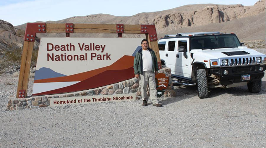 Tourist posing with sign at Death Valley