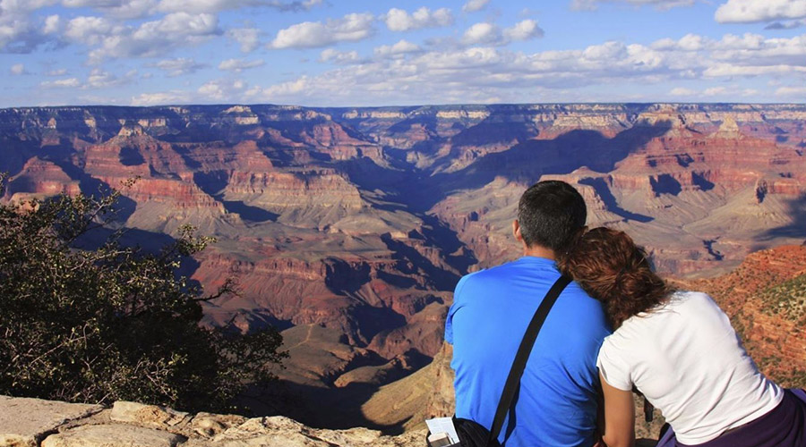 Couple Sitting on Edge of Grand Canyon South Rim